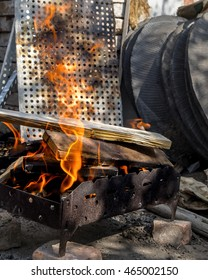 burning wood in a brazier on the background of iron and tires
