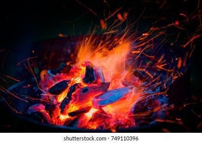 Burning wood and coal in fireplace. Closeup of hot burning wood, coals.