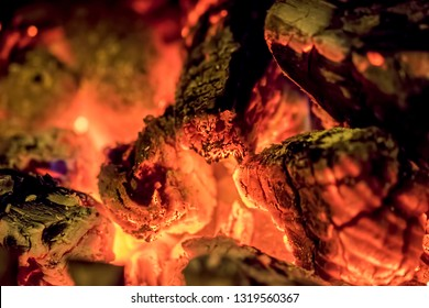 Burning wood embers in close-up. Abstract fire background image of glowing hot wood. Fossil fuel and carbon emissions tax.