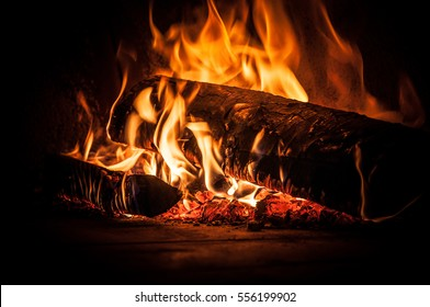 Burning wood inside traditional pizza oven