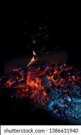 Burning wood at night. Campfire at touristic camp at nature in mountains. Flame amd fire sparks on dark abstract background. Cooking barbecue outdoor. Hellish fire element. Fire roasting coal