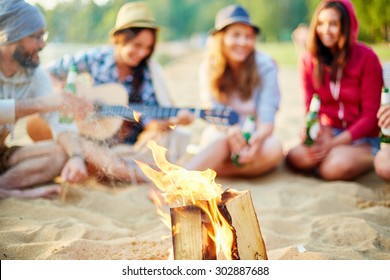 Burning wood on background of restful friends