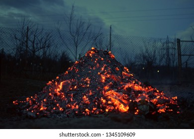 Burning wood pile at night with horror atmosphere. Campfire in the backyard. Flame, fire sparks, glow and ash on dark  background. Hellish fire element.