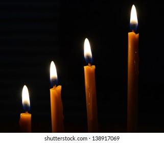 Burning yellow candles isolated on black background