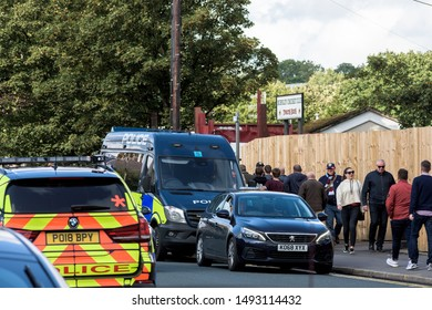 Burnley, Lancashire England UK - August 31, 2019,  Police vehicle parked and football supporters arriving at match between FC Burnley and FC Liverpool on busy street outside a Turf Moor