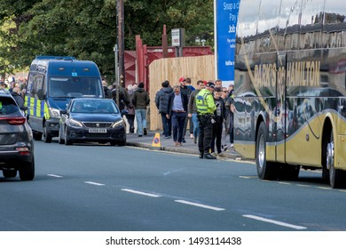 Burnley, Lancashire England UK - August 31, 2019, Police officer checking a young football supporter arriving at match between FC Burnley and FC Liverpool on busy street outside a Turf Moor
