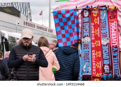 Burnley, Lancashire England UK - August 31, 2019, Supporters and a small shop with clubs memoriables just before a football match between FC Burnley and FC Liverpool on busy street outside a Turf Moor