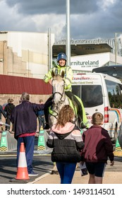 Burnley, Lancashire England UK - August 31, 2019 Mounted police officer on crowd control duty and football supporters arriving at football match between FC Burnley and FC Liverpool outside a Turf Moor