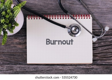 Burnout word on notebook,stethoscope and green plant