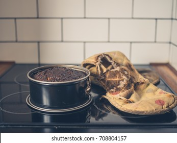 A burnt cake and a burnt oven glove on the cooker