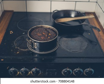 A burnt cake is sitting on a dirty stove