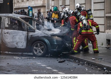 "A burnt car and firefighters extinguishing it during the ""Yellow Vests"" antigovernment protest in the French capital. Paris, France - December 8, 2018"