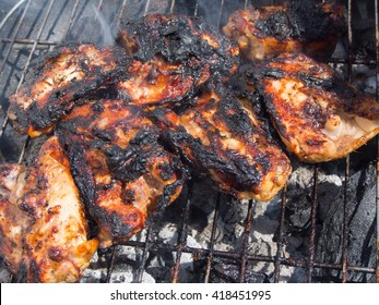 burnt, charred chicken on a barbecue