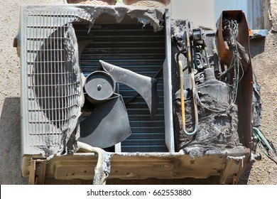 Burnt and charred external air conditioner unit after a fire