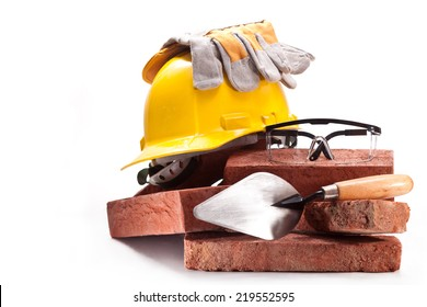 Burnt clay bricks, yellow helmet with gloves, trowel and goggles