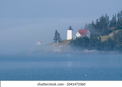 Burnt Coat Harbor lighthouse of Swans Island in Maine, is illuminated by the sun as it breaks through the morning fog. Lighthouse is in the Acadia region in down east Maine.