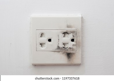 Burnt and damaged electric plug socket from overload short circuit, safety first conception.