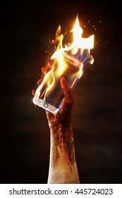 A burnt hand holds a cell phone on fire.