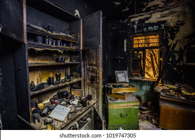 Burnt house interior. Burned kitchen, furniture, door, charred walls and ceiling in black soot.