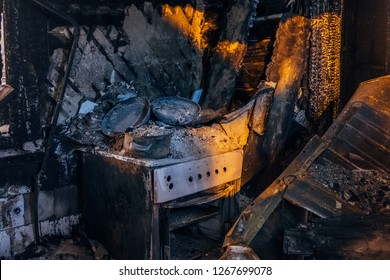 Burnt house interior. Burned kitchen, remains of stove and furniture in black soot.