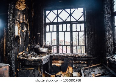 Burnt house interior. Burned kitchen, remains of furniture in black soot.