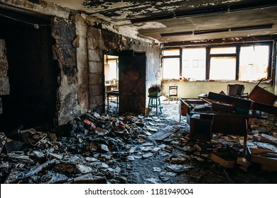 Burnt house interior. Burned room in industrial building, charred furniture and damaged apartment after fire, toned