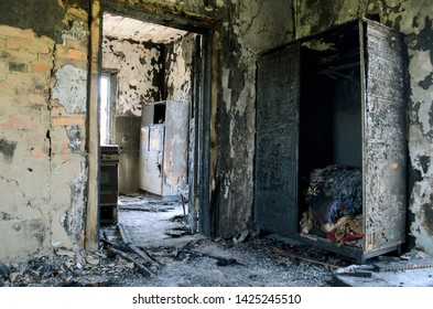 Burnt interior of the house. Interior of the house after the fire, burnt building indoors. Conflagration. Burnt wooden house, view from inside. Wardrobe in the house after the fire.