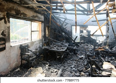Burnt out house with charred roof trusses and burnt furniture