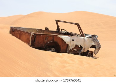 Burnt out and rusting wreckage of a 4WD (four wheel drive) vehicle partially buried in remote arid desert sand dunes in Sharjah, United Arab Emirates. The desert sand is slowly covering the wreckage.