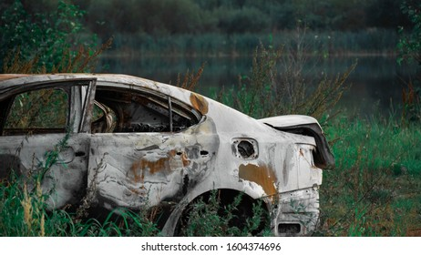 Burnt out, Wrecked car after an explosion or fire. Rusty, burnt car interior with ash, molten glass and metal parts. Abandoned car in the forest near the city. The concept of a traffic accident.