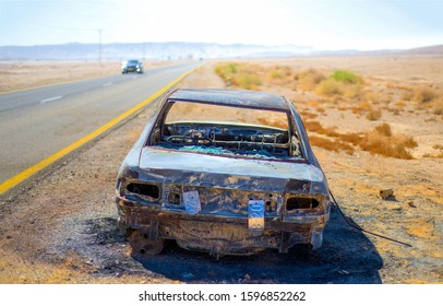 Burnt out wrecked car on side of road. Wrecked car on road. Burnt out car on road. Wrecked burnt out car on side of road