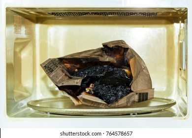 Burnt paper bag with melted and burnt popcorn in the greased and dirty microwave oven, after the explosion and fire