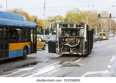 Burnt public traffic bus is seen on the street after caught in fire during travel and extinguished by firefighters.