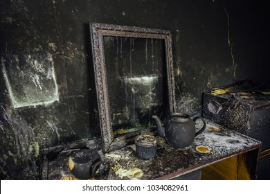 Burnt room interior. Burnt still life. Charred wall, picture frame, pot with burned rose in black soot.