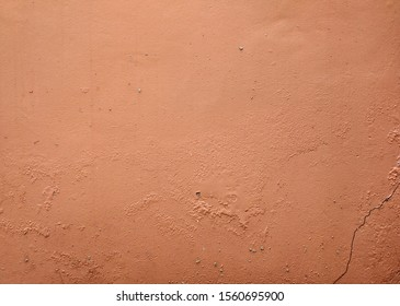 Burnt sienna, terracotta cracked old painted rough textured cement wall background