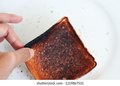 Burnt slice of bread close up in hand on white plate background. Charred food. Wasted life. Hard life. Unsuccessful failure cooking in kitchen. Life mistake depression loe self esteem concept.