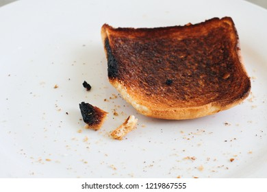 Burnt slice of bread close up on white plate background. Charred food. Wasted life. Hard life. Unsuccessful failure cooking in kitchen. Life mistake depression loe self esteem concept. with copy space