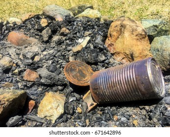 Burnt tin can in fire pit.