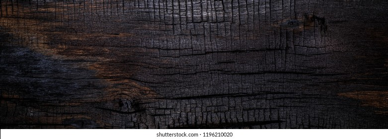 Burnt wooden Board texture. Burned scratched hardwood surface. Smoking wood halloween banner background