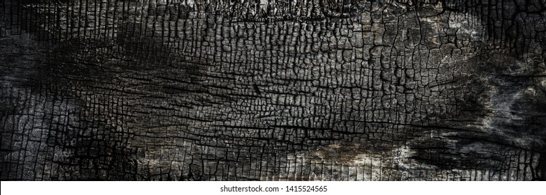 Burnt wooden Board texture. Burned scratched hardwood surface. Smoking wood plank background. BBQ banner background.