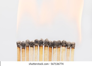 Burnt wooden matches with dark heads and flame above close-up