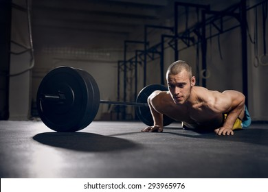 Burpees over the bar - young man training at gym
