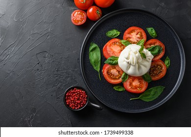 Burrata, Italian fresh cheese made from cream and milk of buffalo or cow. on black plate over black stone surface top view space for text. - Shutterstock ID 1739499338