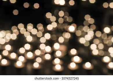 Burring candles on decorative glass. Dark background. Blur and abstract photo.