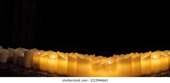 Burring candles on decorative glass. Dark background. Abstract photo.