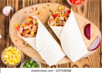 Burrito in tartilla with meat, vegetables, white beans, red pepper, corn. Delicious lunch, Mexican food, homemade snack