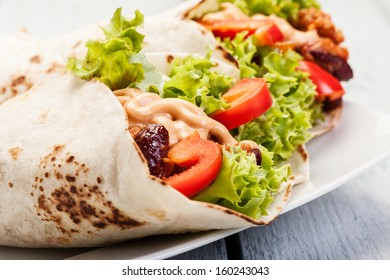 Burrito. Tortilla with meat and beans on a table