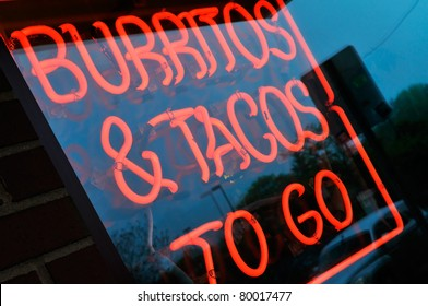 Burritos and tacos to go. Neon store sign on mexican restaurant advertising takeouts
