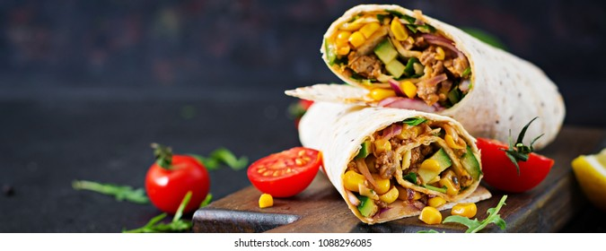 Burritos wraps with beef and vegetables on  black background. Beef burrito, mexican food. Banner