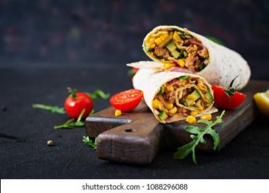 卷饼包裹牛肉和蔬菜在黑色背景。 牛肉卷饼,墨西哥食物。